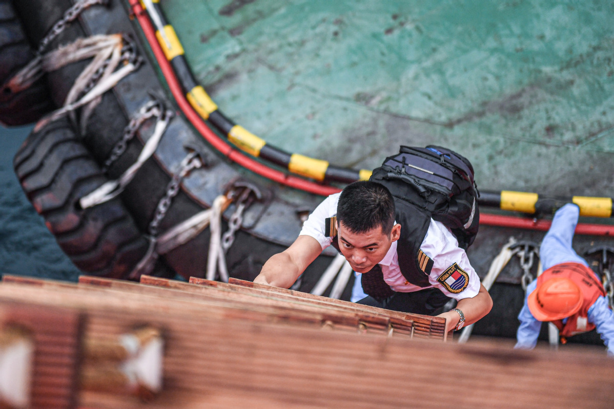 After rushing to an anchorage outside Yangpu Port by tug, pilot Lin Hongpin climbs a large ship on a soft ladder to board and pilot the ship into the port for berthing. [Photo by Pu Xiaoxu/Xinhua]