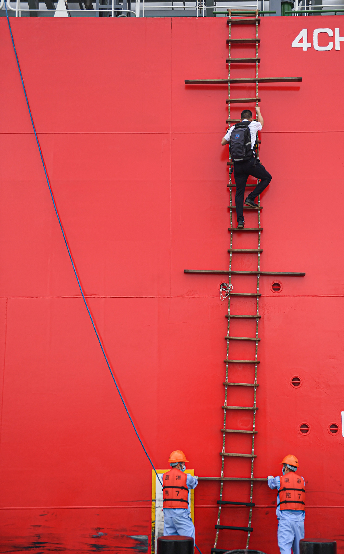 After piloting a large ship into Yangpu Port, Lin Hongpin climbs a tugboat on a soft ladder for other piloting tasks. [Photo by Pu Xiaoxu/Xinhua]