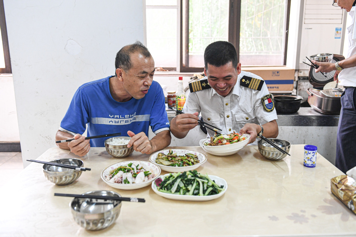 Lin Hongpin (right) returns to the station in Yangpu and chats with Lin Daoming during lunch. [Photo by Pu Xiaoxu/Xinhua]
