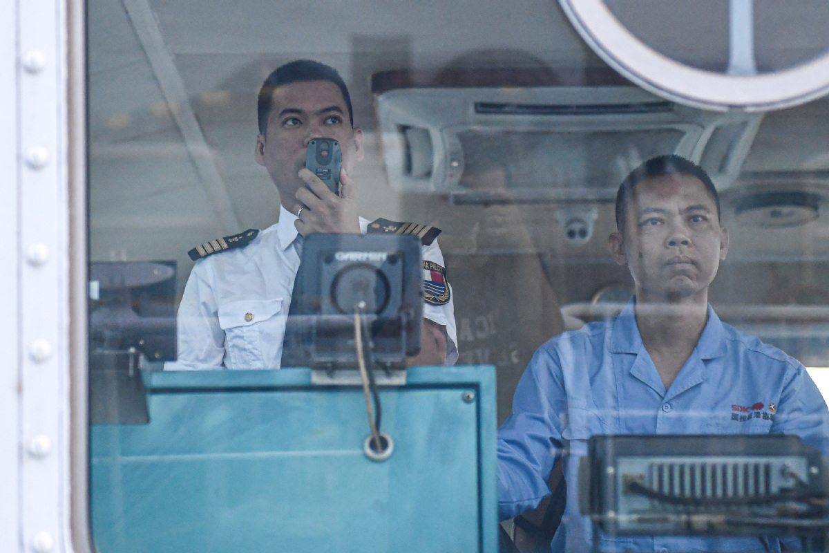 Lin Hongpin (left) uses a walkie-talkie to communicate with the ship he is about to pilot. [Photo by Pu Xiaoxu/Xinhua]